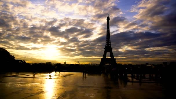 Group of tourist looking at Eiffel Tower with sunset background.