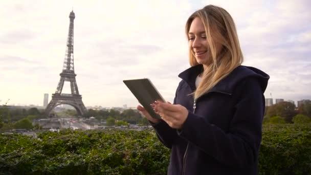 Kosatcových ženské osoby procházející tabletu v blízkosti Eiffel Tower.