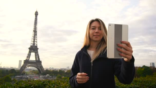 Cheerful woman making video call by tablet with Eiffel Tower background in slow motion.