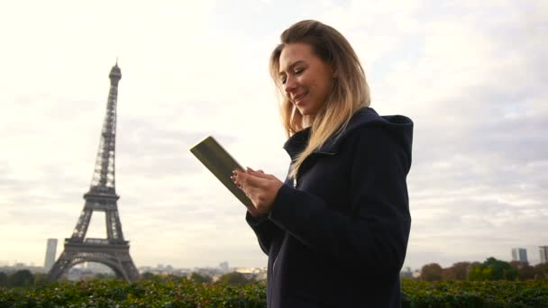 Beautiful woman typing message by tablet with Eiffel Tower background in slow motion.