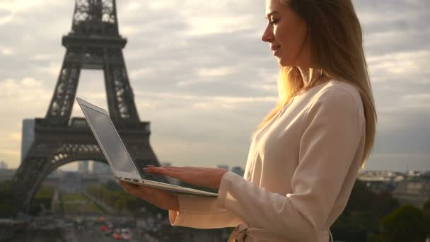 Charming woman chatting by laptop near Eiffel Tower in slow motion.