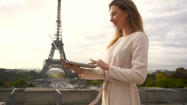Successful businesswoman working with laptop near Eiffel Tower in slow motion.