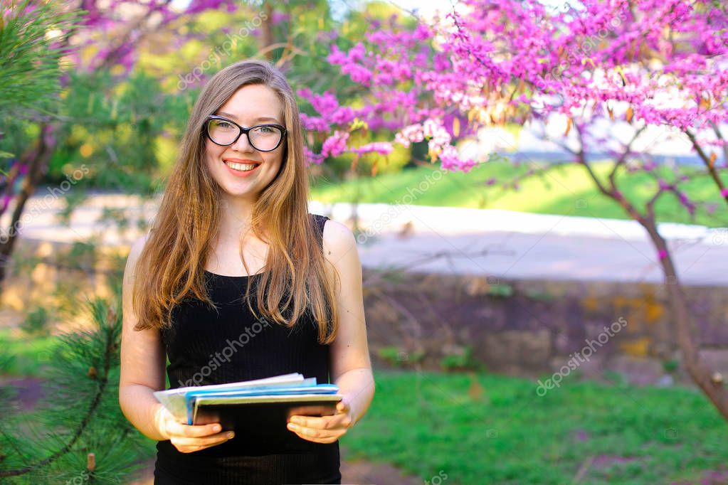 Landscape designer in glasses keeping documents near blooming trees in garden.