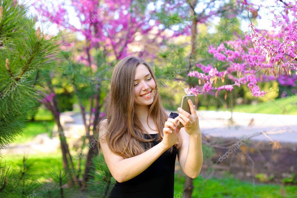 Cheerful girl typing message by smartphone in blooming garden.