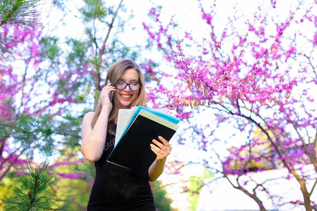 Businesswoman in glasses talking by smartphone in blooming park with documents.