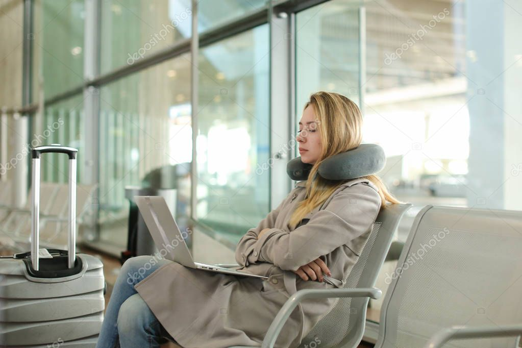 Pretty woman sitting in waiting room with laptop near valise, using neck pillow.