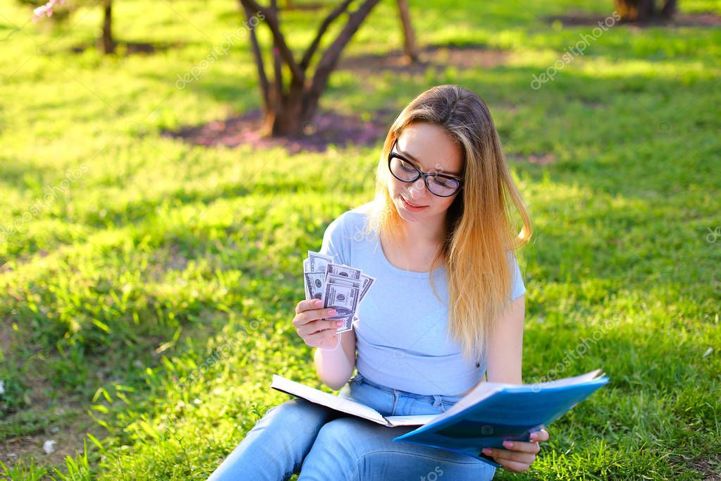 Hard working female student sitting on green grass with documents in park and keeping money.