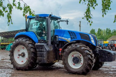 Cherkasy, Ukraine - June 02, 2015:Powerful tractor blue New Holland riding in the mud in the rain