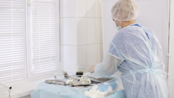 Assistant in operating room checking preparations for surgery