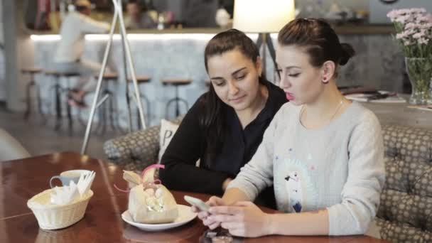 Two young women are talking and using smartphone to show something funny.