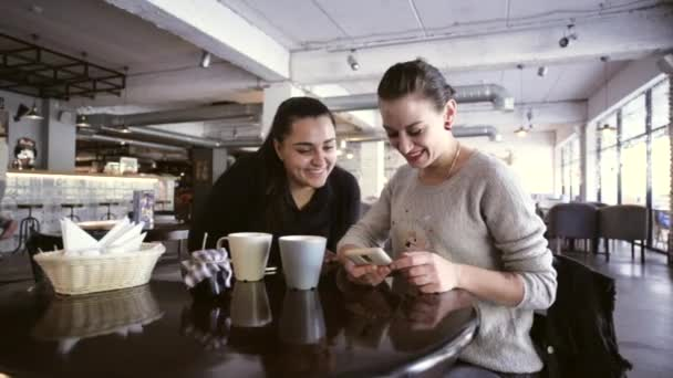 Two female friends sitting at table in cafe looking at mobile phone.