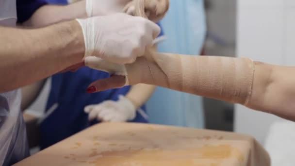 Lékař položí na sádra na ruce pacientka