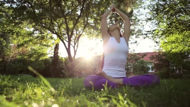 Cvičení jógy. Žena sedí na trávě v parku a meditaci