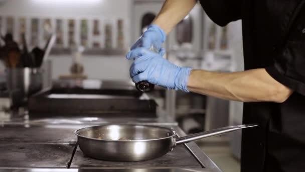 Profesionální kuchař přidání pepř zelenina na pánev