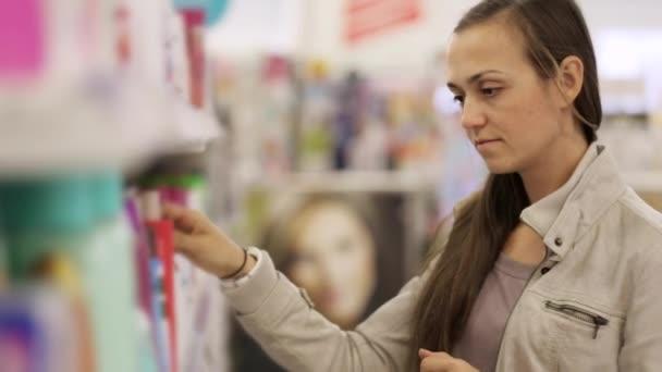 Portrét mladé ženy v bundě čtení popis šamponu v supermarketu