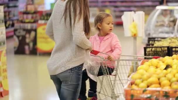 Dcera matka a dítě v supermarketu nákup ovoce a zeleniny