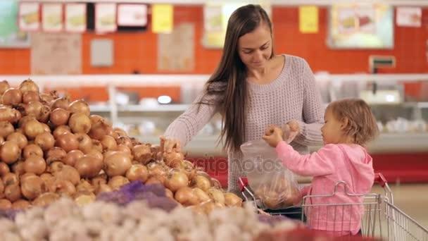 Matka a dcera výběr zeleniny při nakupování v supermarketu