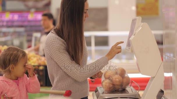 Mladá matka s malým daugher vážení zeleniny a ovoce v supermarketu