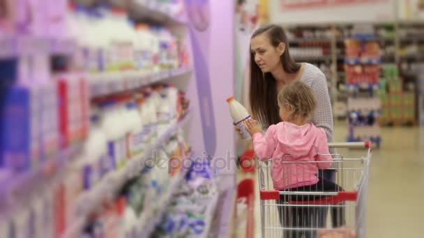 Nő a lánya kitárolási friss tejtermékek a Hűtős részen