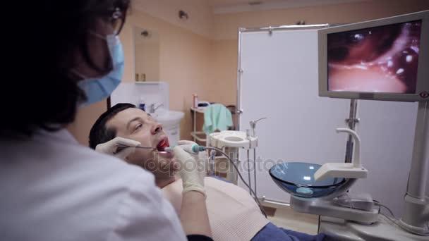 Zubař zkoumání ústa pacienta pomocí intraorální kamery.