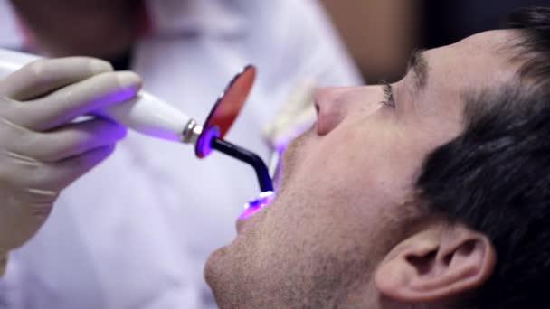 Zahnarzt arbeitet mit Zahnpolymerisationslampe in Dermundhöhle.