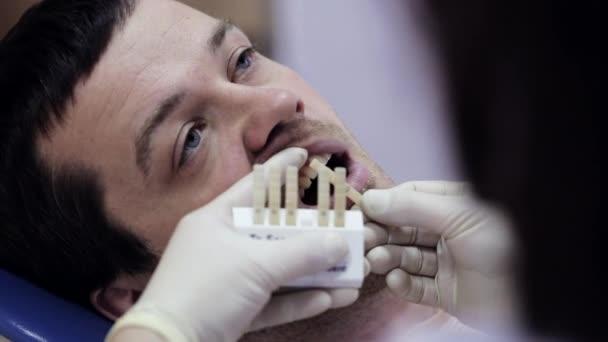 Detail z mladého muže v křesle zubař, zkontrolujte a vyberte barvu zubů.