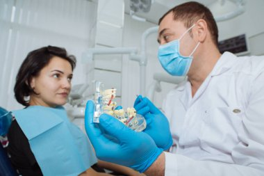 Dentist with patient. Dentist showing a model of teeth.