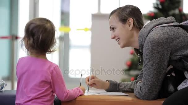 Matka a dcera sedí v čekací hale na letišti s cvičebnice