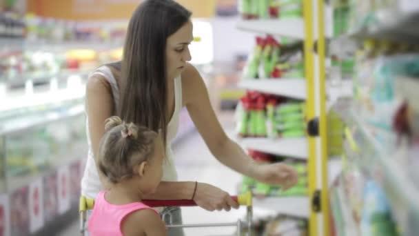 Mladá žena s roztomilý dcera výběr rostlinných olejů s potravinami nákupní centrum