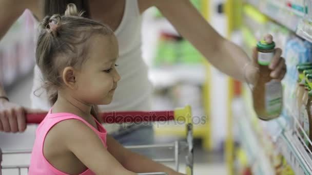 Young woman with cute daughter choosing a sauce in grocery shopping mall