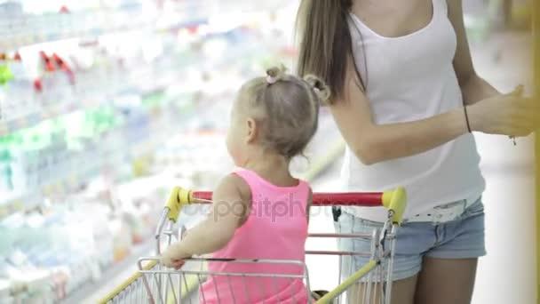 Holčička je sedět v batole když její matka výběrem zboží v supermarketu