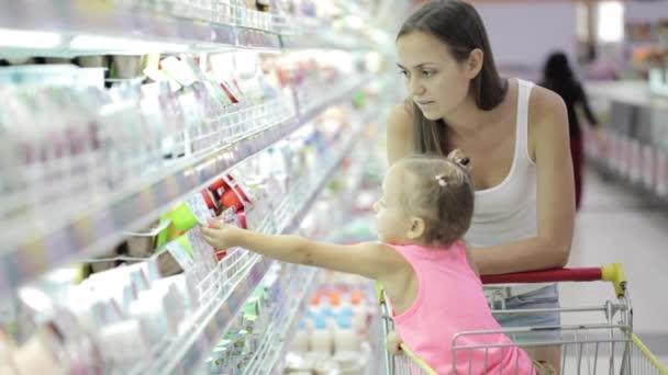 Mladá žena s roztomilý dcera vybrat jogurt s potravinami nákupní centrum