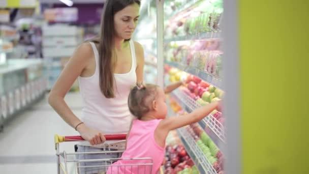 Žena a malá holčička výběr ovoce při nakupování v supermarketu