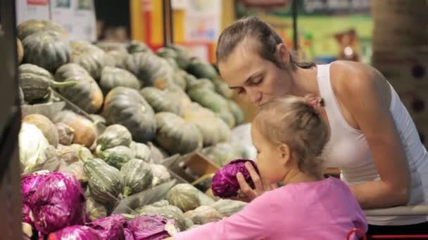Giovane madre con la piccola figlia nel carrello selezionando verdure al supermercato