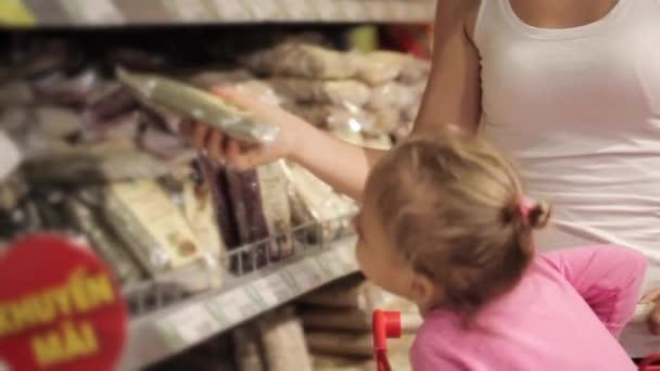 Atraktivní mladá žena s dcerou nakupovat v supermarketu