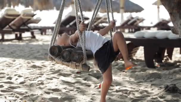 Cute baby girl playing and doing gymnastic exercise on the swing at sandy beach