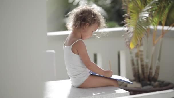 Dívka nakreslit tužkou na papíře na balkón s palmami v pozadí