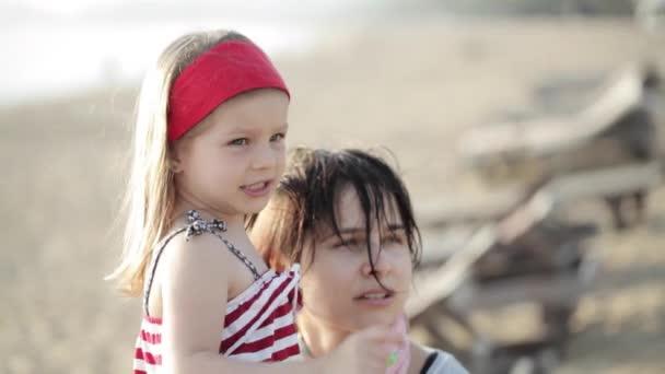 Ritratto di giovane madre graziosa e piccola figlia sulla spiaggia