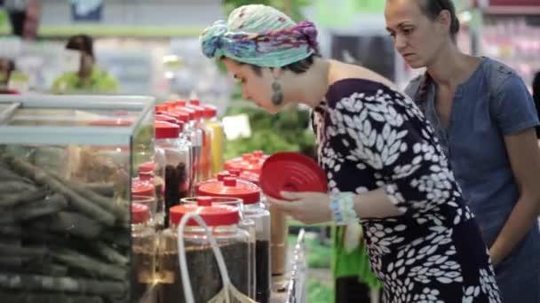 Dvě mladé Zenske výběr koření v části potravin v supermarketu