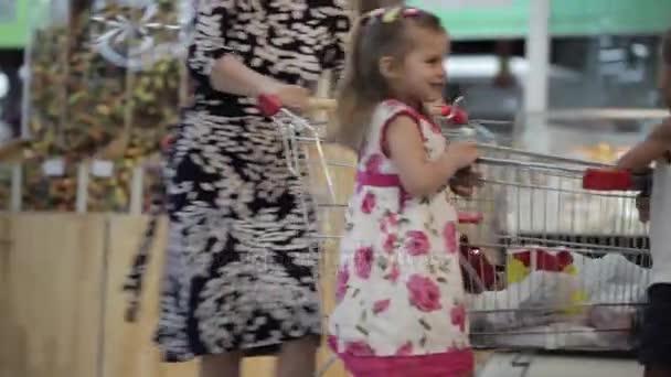 Famiglia divertendosi nel centro commerciale Guida un carrello della spesa