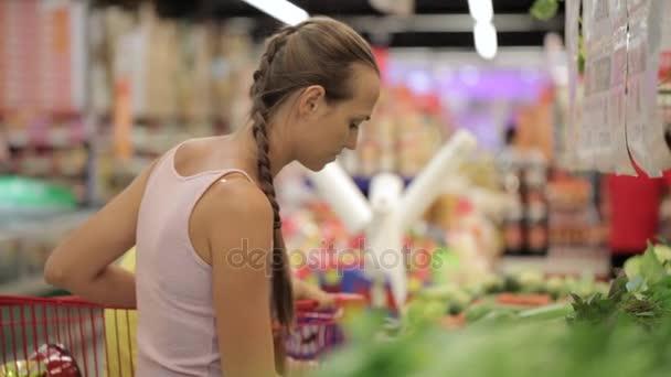 Giovane madre con la piccola figlia nel carrello selezionando verdi al supermercato