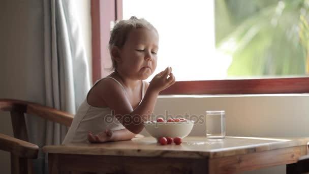 Kis lány ül a asztal és étkezési cseresznye paradicsom