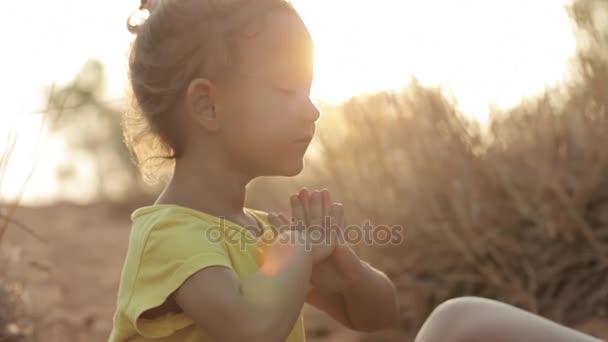 Mutter und Tochter meditieren bei Sonnenaufgang
