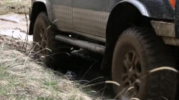 Oříznout exprditionary Suv pomalu jezdí na horské silnici špinavé