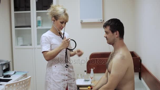 Zdravotní sestra poslouchá mužský pacient přes phonendoscope.