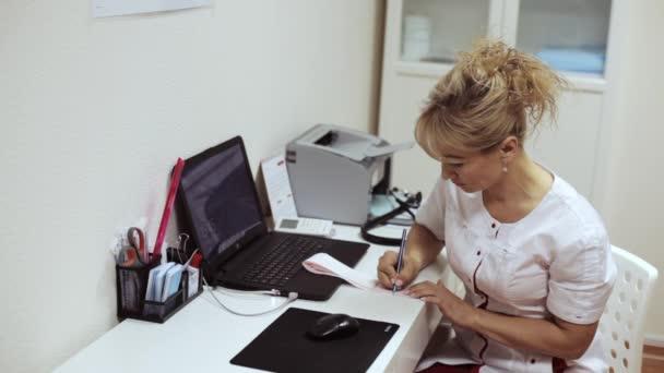Ärztin sitzt am Tisch und schreibt über Ergebnisse des Elektrokardiogramms.