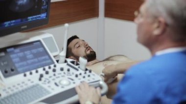 Doctor radiologist examining abdomen of male patient with ultrasound.