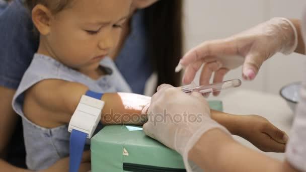 kleines Mädchen mit Mutter im Krankenhaus. Krankenschwester entnimmt Mädchen venöses Blut für Test