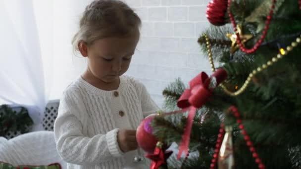 Nettes kleines Mädchen schmückt den Weihnachtsbaum.