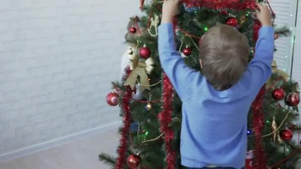 Děti zdobí vánoční strom ve světlé místnosti ve dne